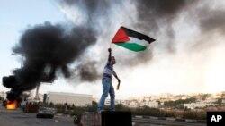 Un Palestinien fait flotter le drapeau national durant une manifestation près de Ramallah, le 18 nov. 2012
