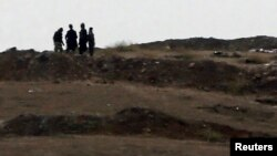Armed men, presumed to be Islamic State fighters, stand at a checkpoint in the west of Syrian town of Kobani, seen from near the Mursitpinar border crossing on the Turkish-Syrian border, Oct. 13, 2014.