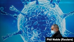 Great Britain, A man wearing a protective face mask walks past an illustration of a virus outside a regional science centre