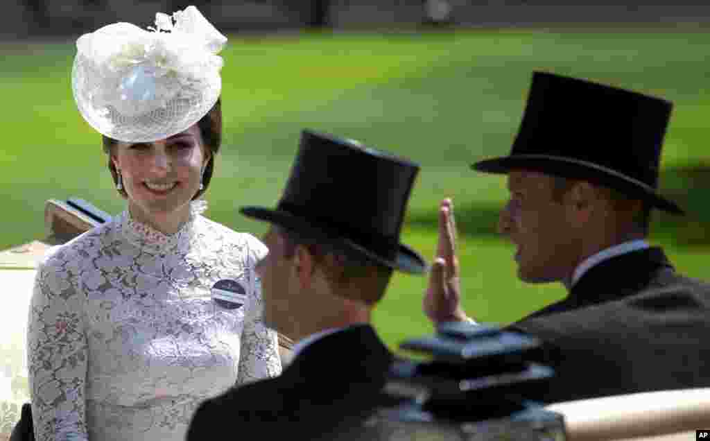 Britain's Kate, Duchess of Cambridge, left, smiles as she travels with Prince William, right and Prince Edward, in a open carriage to the parade ring on the first day of the Royal Ascot horse race meeting in Ascot, England.