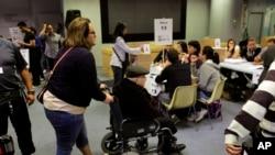 2013年4月14日委内瑞拉总统选举日设在西班牙马德里的一个投票站里,一名妇女设法帮助一位旅居西班牙,坐着轮椅的委内瑞拉人投票选举总统。