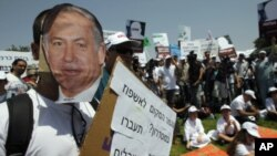 A protester wears a mask depicting Israel's Prime Minister Benjamin Netanyahu during a rally in front of the Knesset, the Israeli parliament, in Jerusalem July 31, 2011
