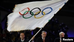 Rio de Janeiro Mayor Eduardo Paes (L) waves the Olympic Flag with IOC President Jacque Rogge (C) and London Mayor Boris Johnson (R) during the closing ceremony of the London 2012 Olympic Games at the Olympic Stadium, August 12, 2012.