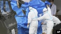 日本自衛隊員星期五在福島核電站把踏入受核污染的水中的工人轉移