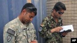 Sergeant First Class David Lara is putting Afghan Air Force flight medics through their paces as he works with Afghan Air Force Sergeant Hayatullah Bahar, Aug 2010