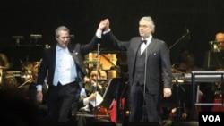 Andrea Bocelli, derecha, de la mano del director de la orquesta Eugene John durante el concierto en Washington. [Foto: Mitzi Macias, VOA].
