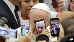 Wajah Paus Fransiskus terhalang telepon genggam para pengunjung yang ingin memotretnya saat memasuki aula Paus Paulus VI di Vatikan, Roma, 9 Januari 2019.
