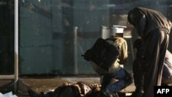 """Архив: эксперты-криминалисты осматривают тело погибшего при теракте в """"Домодедово"""""""