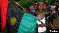 FILE - A man carries the Biafran flag during a parade in Ekwe village, near Enugu in southeastern Nigeria, May 27, 2008.