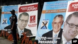A private security guard stands in front of campaign signs of Otto Perez Molina, presidential candidate of the Patriotic Party, center, and Manuel Baldizon, presidential candidate of the Democratic Freedom Revival party in Guatemala City, November 5, 2011