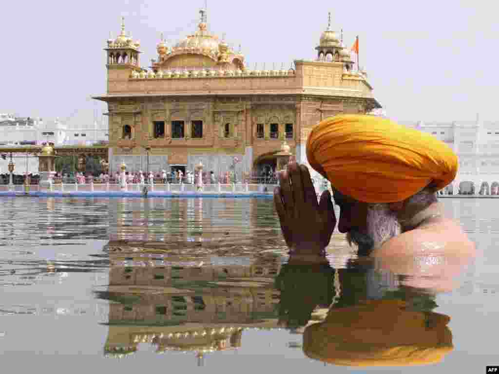 An Indian Sikh devotee takes a holy dip in the sarover (water tank) at the Golden Temple in Amritsar.