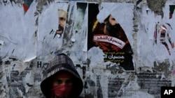 Seorang pengunjuk rasa anti-pemerintah Bahrain melindungi wajahnya dari semprotan gas air mata yang ditembakkan oleh polisi anti huru-hara di depan poster eksekusi ulama Syiah di Arab Saudi.