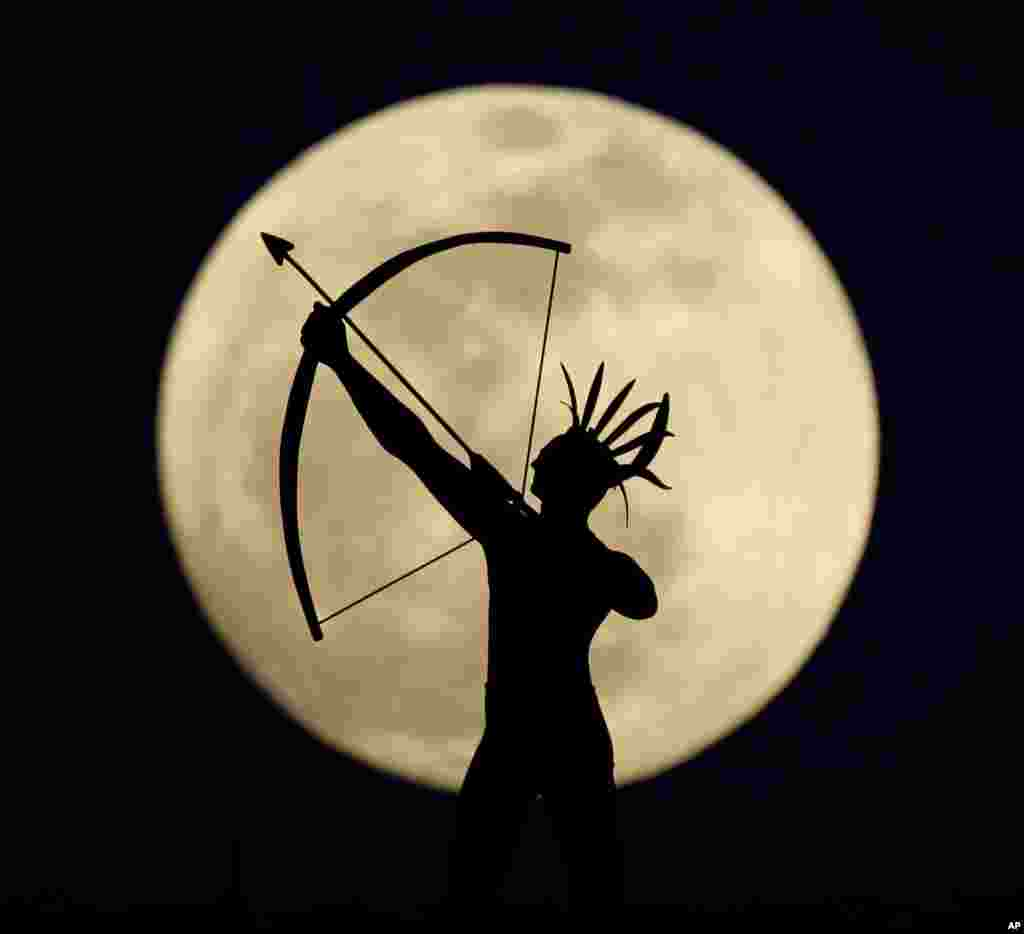 A full moon rises behind a statue of a Kansas Indian on top of the Kansas Statehouse in Topeka, Kansas, USA, Apr. 24, 2013.