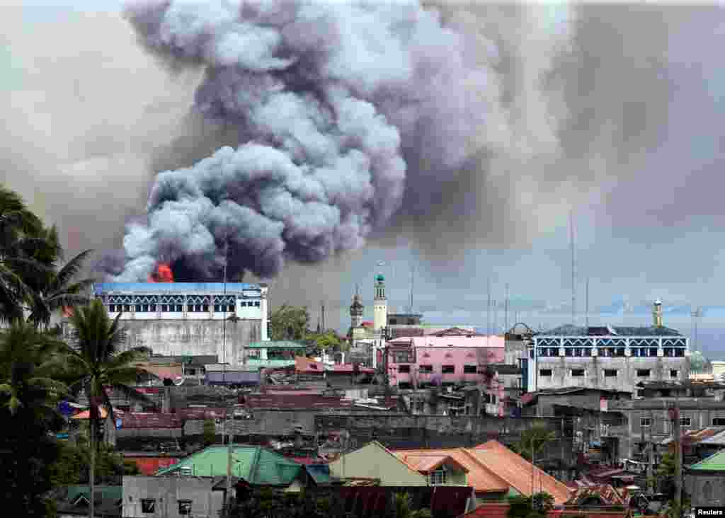 Black smoke billows from a burning building in a commercial area of Osmena street in Marawi city, Philippines.