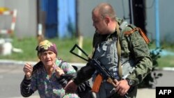 Seorang separatis pro-Rusia membantu seorang perempuan menghindari serangan pasukan Ukraina di Donetsk, Ukraina timur (21/7).