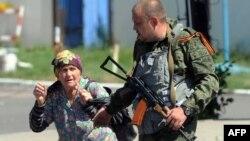 21일 우크라니아 동부 도네츠크에서 친러 분리주의 반군 병사가 폭격을 피해 달아나고 있는 한 노인과 함께 걷고 있다.