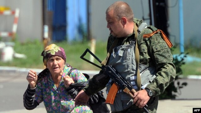 An armed pro-Russia separatist walks with a woman fleeing shelling near the train station in Donetsk, Ukraine, on July 21, 2014.