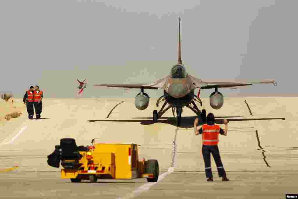 A ground crew member directs an Israeli F-16 fighter jet after it landed at Ovda airbase, some 40 km (25 miles) north of Eilat, during the Blue Flag drill. The Blue Flag drill is a two-week multilateral air force drill with air forces of Israel, the United States, Greece and Italy.