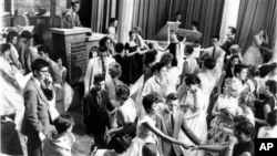 """Dick Clark, at upper left, is surrounded by teenage fans on his nationally televised dance show """"American Bandstand"""" in 1958"""