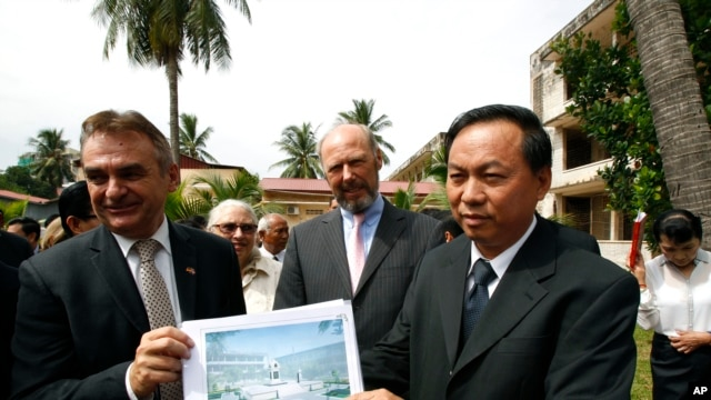 Cambodian official Han Touch (r) and German Embassy officer Adelbert Eberhardt hold a design of a memorial building as Joachim Baron Von Marschall, center, German Ambassador to Cambodia, watches at the building site, at the Tuol Sleng Genocide Museum, in in Phnom Penh, Cambodia, July 10, 2014.