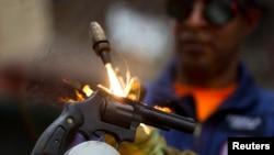 Un trabajador destruye un arma confiscada en Caracas.