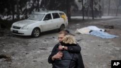 30일 우크라이나 동부 도네츠크에서 한 반군 병사가 폭력사태로 남편을 잃은 미망인을 위로하고 있다.