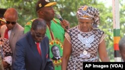 FILE: Zimbabwean President Robert Mugabe, left, is assisted by his wife Grace to get off the stage after addressing supporters at the party headquarters in Harare, Wednesday Feb, 10, 2016.