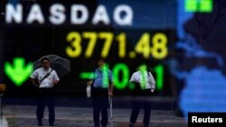 Businessmen are reflected on a board showing the U.S. NASDAQ average outside a brokerage in Tokyo, Oct. 1, 2013.