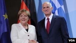 Kanselir Jerman Angela Merkel dan PM Yunani Georgios Papandreou berjabat tangan sebelum melakukan pembicaraan dan makan malam bersama di Berlin, Jerman (27/9).