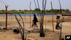 FILE - Chadian women walk past destroyed homes, in the Lake Chad shore village of N'Gouboua. Guerrillas have recently ramped up attacks in remote border areas around Lake Chad.