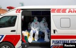 Petugas medis mengenakan pakaian pelindung di dalam ambulans setelah mengumpulkan sampel usap untuk pengetesan virus corona (Covid-19) di pasar tradisional di Jakarta, 2 Juli 2020. (Foto: Reuters)