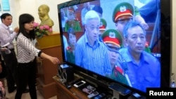 Phóng viên đặt thiết bị ghi âm cạnh màn hình TV trực tiếp từ phòng xử án tại Hà Nội, nơi ông Nguyễn Ðức Kiên bị xét xử, ngày 16/4/2014.