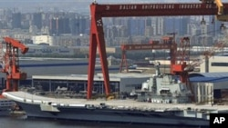 In this photo taken on Aug. 6, 2011, a Chinese aircraft carrier, which had been under refurbishment, is docked at Dalian port in in northeastern Liaoning province.