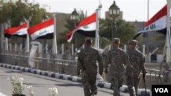 Tentara AS melewati 'Camp Victory' yang berbendera Irak, setelah serah terima dari AS kepada Irak di Baghdad (1/12).