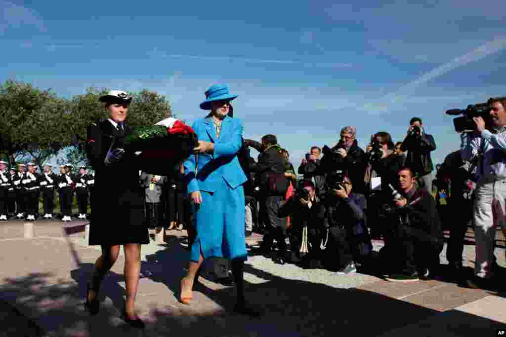 Queen Margrethe of Denmark lays a wreath in front of a war memorial, as part of D-Day commemorations, at Sainte Marie du Mont, France, June 6, 2014.