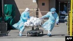 အေမရိကန္ႏိုင္ငံ New York ၿမိဳ႕ရွိ ေဆးရံုတခုမွာ COVID - 19 လူနာတဦးကို သယ္ေဆာင္သြားတဲ့ က်န္းမာေရး ၀န္ထမ္းမ်ား။ (ဧၿပီ ၀၆၊ ၂၀၂၀)
