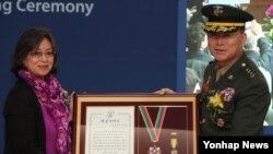 19일 서울 중구 세브란스빌딩에서 열린 고(故) 현봉학 박사 동상 제막식에서 현 박사의 장녀 에스더 씨가 현 박사를 대신해 이상훈 해병대 사령관으로부터 해병대 핵심가치상을 받고 있다.