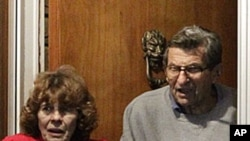 Joe Paterno and his wife, Susan, come to the doorway of their home to thank supporters gathered outside their home after John Surma, chairman and chief executive officer, announced the firing of Paterno as head football coach, November 9, 2011.