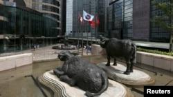 香港交易廣場水牛雕塑前香港證券交易所的旗子在飄揚。(資料圖片)