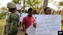 Masu zanga zangar nuna rashin amincewa cire tallafin mai, ke wuce wani soja dake gadi a Abuja baban birnin taraiyar Nigeria.