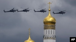 Russian military helicopters fly over the Ivan the Great bell-tower and Kremlin during a rehearsal in Moscow, Russia, May 5, 2016.