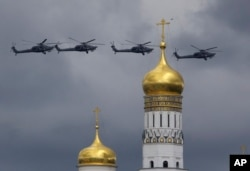 "FILE - Russian military helicopters fly over Ivan the Great bell-tower and Moscow's Kremlin, May 9, 2016. A Washington-based think tank launched the Kleptocracy Archive, a database that enables users to ""identify key actors in the complicated patronage and business networks that characterize kleptocracies."""