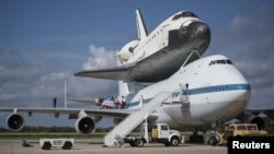Workers pose for a photograph on the wing of NASA's Shuttle Carrier Aircraft, with the space shuttle Endeavour mated on top, at the Kennedy Space Center in Cape Canaveral, Florida, September 18, 2012.