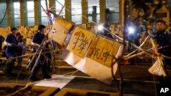 Полицейский спецназ разбирает баррикады на улицах Гонконга. 17 октября 2014 г.