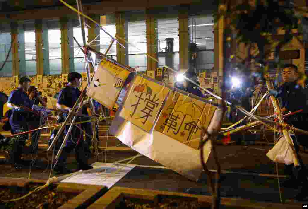 Riot police remove barricades in the Mong Kok district of Hong Kong, early Friday, Oct. 17, 2014.