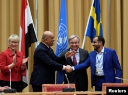 Head of Houthi delegation Mohammed Abdul-Salam (R) and Yemeni Foreign Minister Khaled al-Yaman (2 L) shake hands next to United Nations Secretary General Antonio Guterres and Swedish Foreign Minister Margot Wallstrom (L), during the Yemen peace talks in Sweden, Dec 13, 2018.
