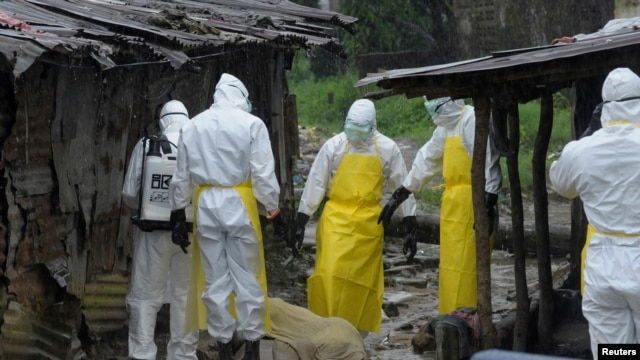 Health workers wearing protective clothing prepare to carry an abandoned dead body presenting with Ebola symptoms at Duwala market in Monrovia August 17, 2014.