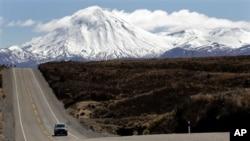 Sebuah mobil melintasi jalanan didekat gunung Tongariro yang diselimuti salju di Selandia Baru (Foto: dok). Gunung Tongariro meletus Senin petang (6/8) menyemburkan abu setinggi 6.000 meter.