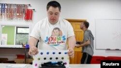 John Cronin, seorang penderita Down Syndrome dan salah satu pendiri John's Crazy Socks, sebuah toko kaus kaki online yang mendonasikan persentase dari hasil penjualannya ke lembaga-lembaga amal yang membantu penyandang disabilitas, tampak sedang membungkus pesanan kaus kaki di kantor pusat perusahaan tersebut di Melville, New York, AS, 23 Juli 2018 (foto: REUTERS/Shannon Stapleton)