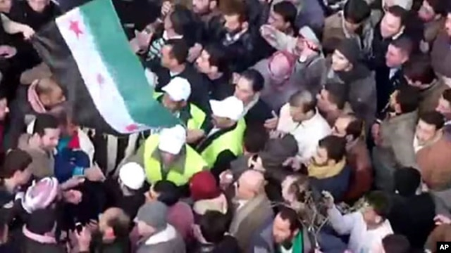 In this image from amateur video made available by the Shaam News Network and shot on Friday, Dec. 30, 2011, Arab League observers are seen at a protest in Idlib, Syria.